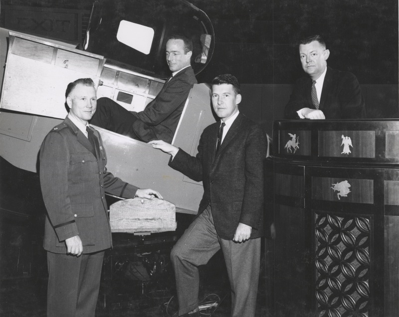 Photograph of Col. Cage, Scott Carpenter (in a Link trainer), Wally Schirra, and Morehead astronaut trainer James Batten. Black and White 8x10 Photographic Print 50075_0003 in the University of North Carolina at Chapel Hill Photographic Laboratory Collection #P0031, North Carolina Collection Photographic Archives, The Wilson Library, University of North Carolina at Chapel Hill.